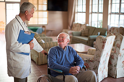 Doctor talking to patient in wheelchair - p555m1305754 by Resolution Productions