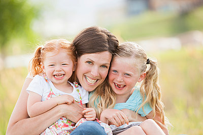 Caucasian mother and daughters smiling outdoors - p555m1453258 by Mike Kemp