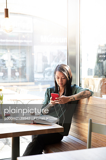 Woman with earbuds and cell phone in a cafe - p300m2139942 by Florian Küttler