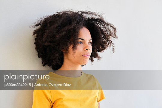 Curly hair student looking away while leaning on white wall - p300m2242215 by Antonio Ovejero Diaz