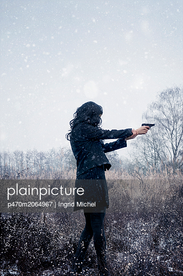 Woman holding a pistol - p470m2064967 by Ingrid Michel