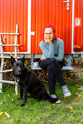 Portrait of content senior woman with red dyed hair sitting in front of red trailer in the garden with her dog - p300m2081292 by Julia Otto