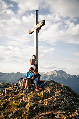 Austria, Tyrol, mother and son on a hiking trip with book at the summit - p300m2083334 von Florian Küttler