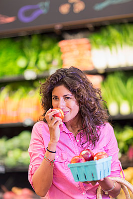 Hispanic woman checking produce at grocery store - p555m1411402 by Marc Romanelli