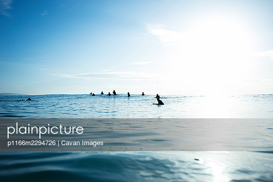surfers waiting for a wave, in the sea, surf, sky - p1166m2294726 by Cavan Images