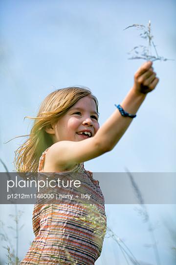 Mädchen bastelt mit Grashalmen und Wildblumen - p1212m1146000 von harry + lidy