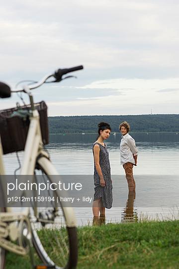 Junges Paar im See - Fahrrad - p1212m1159194 von harry + lidy