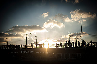 Silhouettes of people passing on Galatta bridge at sunset - p1007m1134853 by Tilby Vattard