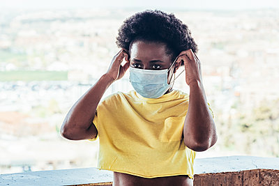Portrait of an African American black girl putting on her face mask. - p1166m2269128 by Cavan Images