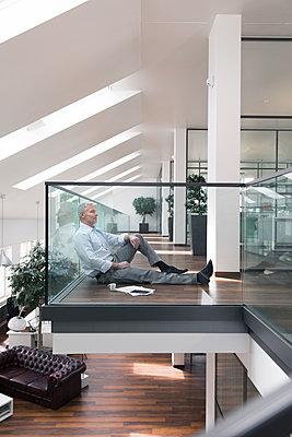 Businessman sitting on floor in the office, taking a break - p300m1537445 by Florian Küttler