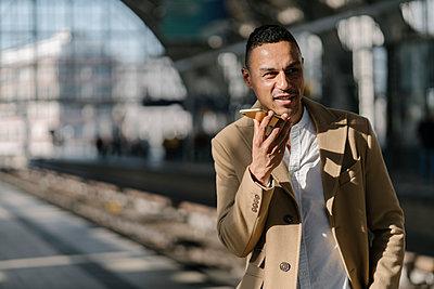 Portrait of businessman on the phone standing on platform of train station Alexanderplatz, Berlin, Germany - p300m2143378 von Hernandez and Sorokina