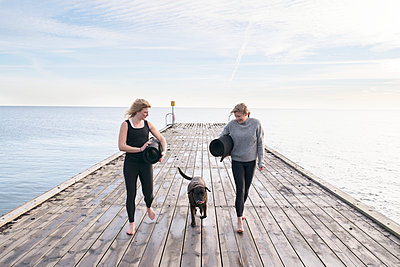 Women walking with dog on pier - p312m1470779 by Viktor Holm