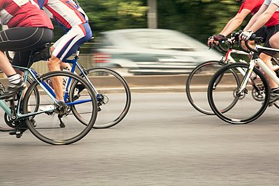 Neck down view of four racing cyclists speeding on urban road in racing cycle race - p429m1118473f by Seb Oliver