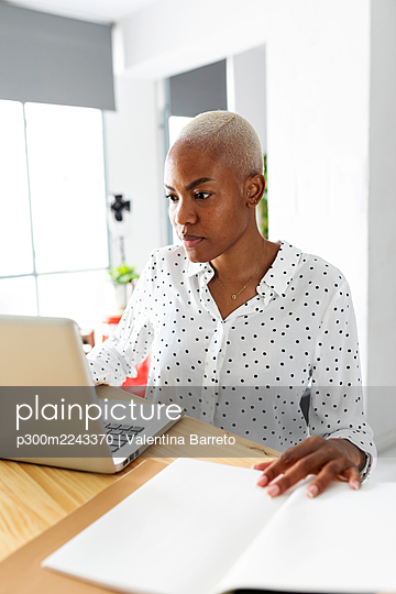 Businesswoman working in modern office with laptop using notes - p300m2243370 by Valentina Barreto