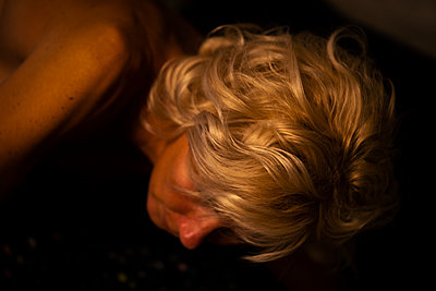A blond haired woman in bed at night. - p1166m2088385 by Cavan Images