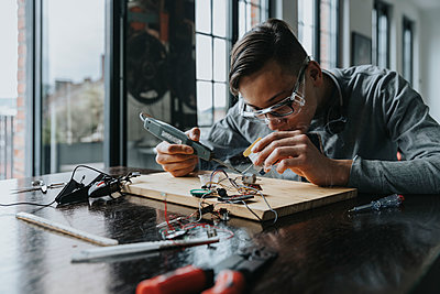 Young man tinkering with soldering iron at home - p300m2214091 by Mareen Fischinger