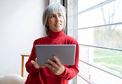 Smiling mature woman looking away while holding digital tablet at home - p300m2277251 by Jose Carlos Ichiro