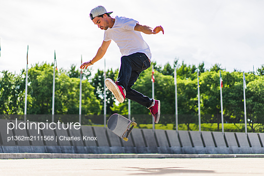 Young skateboarder doing a flip trick on ground, Montreal, Quebec, Canada - p1362m2111568 by Charles Knox