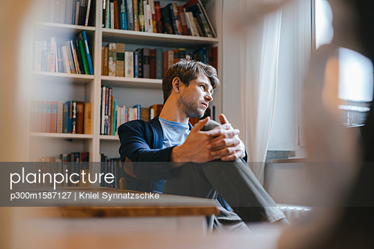 Man sitting at bookshelf looking sideways - p300m1587127 von Kniel Synnatzschke