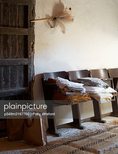 Folded bedding on cinema chairs with feather duster in  Sicilian home - p349m2167760 by Polly Wreford