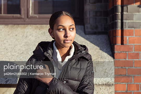 Thoughtful teenage girl wearing jacket looking away while sitting against wall - p426m2149302 by Kentaroo Tryman