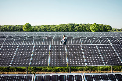 Mature man using smartphone standing on panel in solar plant - p300m2004597 by Robijn Page