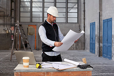 Male architect analyzing blueprint while standing at table in building - p300m2244181 by Veam