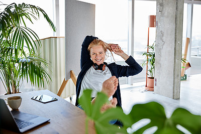 Smiling female entrepreneur with hands behind head relaxing on chair at desk in home office - p300m2265221 by Jo Kirchherr