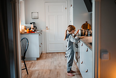 Smiling girl cooking in kitchen - p312m2237248 by Anna Johnsson