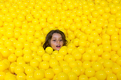 Head of girl among yellow balls - p756m1464834 by Bénédicte Lassalle