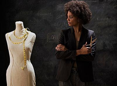 Businesswoman with tailors dummy holding scissors - p924m742207 by Jose Luis Pelaez Inc.
