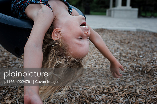 Carefree cheerful girl lying on outdoor play equipment while playing at playground during autumn - p1166m2024791 by Cavan Images