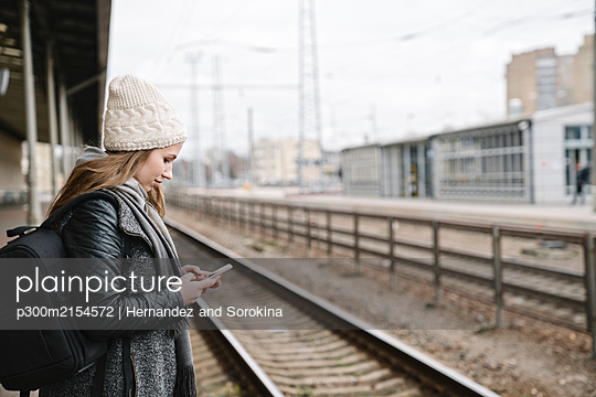Smiling young woman with backpack standing on platform using cell phone - p300m2154572 by Hernandez and Sorokina