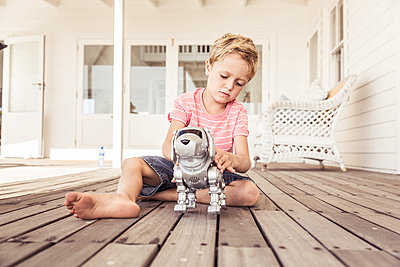 Boy playing with robot dog on veranda - p300m2167001 by Floco Images
