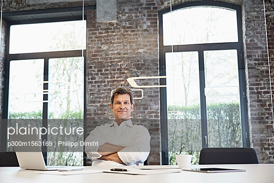 Portrait of mature businessman with laptop in modern office - p300m1563169 by Philipp Dimitri