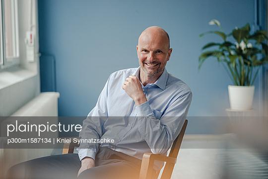 Portrait of smiling mature businessman sitting in chair - p300m1587134 von Kniel Synnatzschke