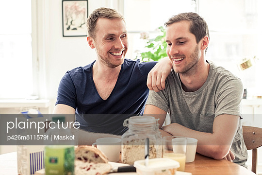 Happy homosexual couple communicating while having breakfast together at table in home