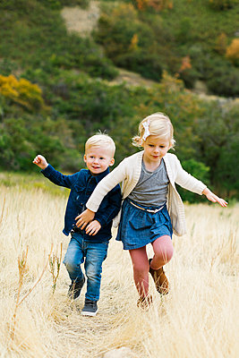 Boy and girl running in field - p1427m2038235 by Jessica Peterson