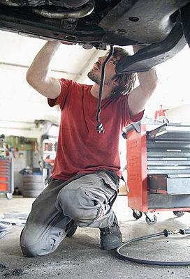 Germany, Ebenhausen, Mechatronic technician working in car garage - p300m1188758 by Tom Chance