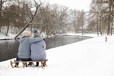 Couple embracing while sitting on sled near lake during winter - p300m2281801 by Frank van Delft