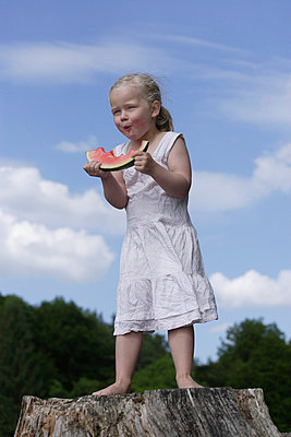 Girl eating piece of watermelon - p300m730533f by Tom Chance