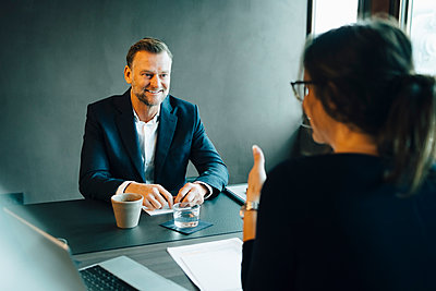 Smiling male entrepreneur listening to female colleague at conference table in board room - p426m2270849 by Maskot
