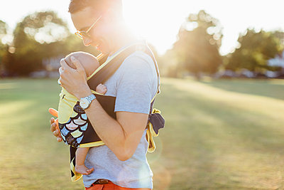 Father carrying baby boy in baby carrier - p429m1569551 by Katie Rollings