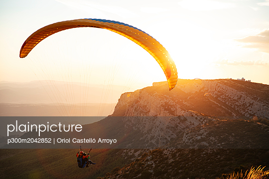 Spain, Silhouette of paraglider soaring high above the mountains at sunset - p300m2042852 von Oriol Castelló Arroyo