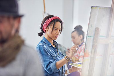 Focused female artist painting at easel in art class studio - p1023m1506506 by Rafal Rodzoch