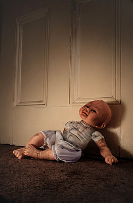 Broken doll propped against door - p1072m829360 by Neville Mountford-Hoare