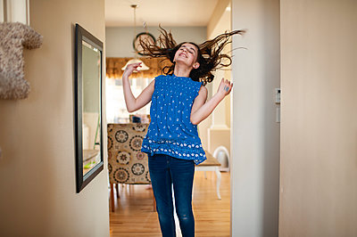 Teen girl jumping and flipping her hair in front of mirror at home - p1166m2137309 by Cavan Images