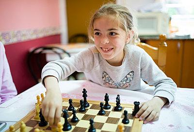 Little girl playing chess - p300m1153487 by Ramon Espelt