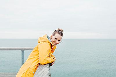 Young woman wearing yellow rain coat - p300m2140639 by sinanmuslu