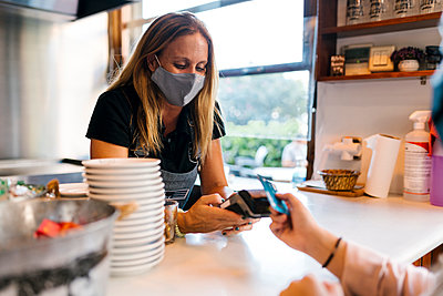 Female cashier in face mask receiving payment through credit card in cafe during COVID-19 - p300m2220724 by Ezequiel Giménez